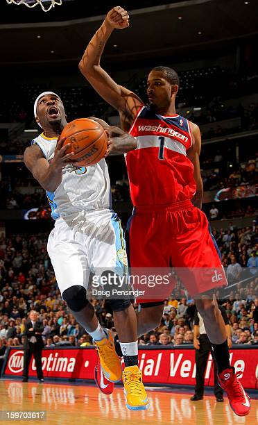 Ty Lawson of the Denver Nuggets lays up a shot against Trevor Ariza of the Washington Wizards at the Pepsi Center on January 18 2013 in Denver...