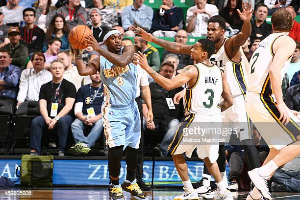 Ty Lawson of the Denver Nuggets looks to pass around Trey Burke of the Utah Jazz at EnergySolutions Arena on December 01 2014 in Salt Lake City Utah...