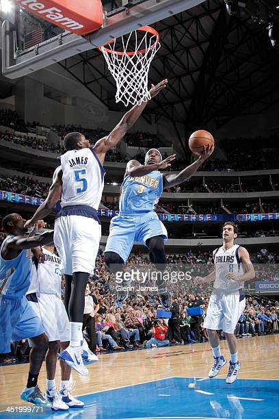 Ty Lawson of the Denver Nuggets shoots against Bernard James of the Dallas Mavericks on November 25 2013 at the American Airlines Center in Dallas...