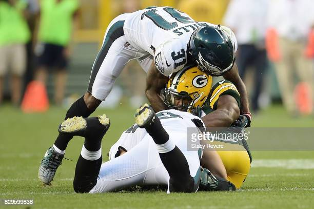 Ty Montgomery of the Green Bay Packers is brought down by Joe Walker and Jalen Mills of the Philadelphia Eagles during the first quarter of a...