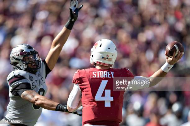 Ty Storey of the Arkansas Razorbacks throws a pass in the first half under pressure from Montez Sweat of the Mississippi State Bulldogs at Davis Wade...