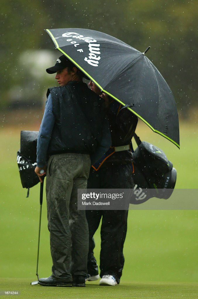 Ty Tryon of the USA takes cover behind an umbrella from heavy rain during the first round of the Ericcson Masters Golf held at the Huntingdale Golf Club in Melbourne, Australia on December 5th, 2002. (Picture by Mark Dadswell/Getty Images).