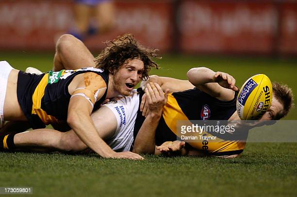 Ty Vickery and Jack Riewoldt of the Tigers fall to the ground during the round 15 AFL match between the North Melbourne Kangaroos and the Richmond...