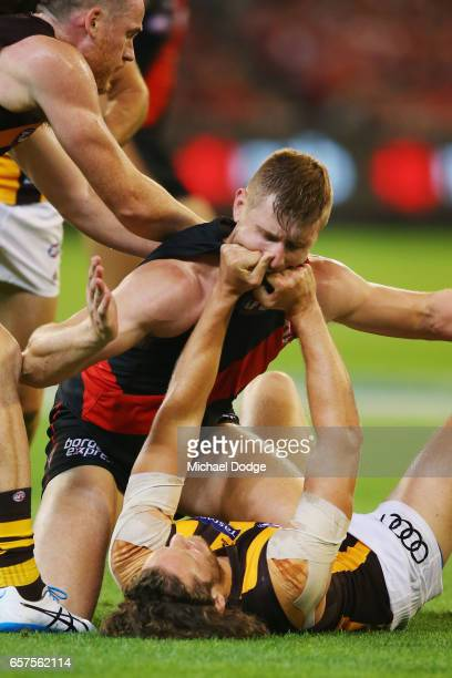 Ty Vickery of the Hawks gives Shaun McKernan of the Bombers a jumper punch during the round one AFL match between the Essendon Bombers and the...