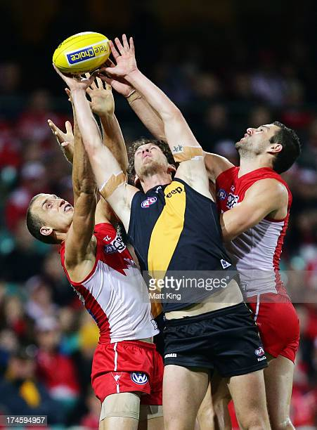 Ty Vickery of the Tigers is challenged by Ted Richards and Josh Kennedy of the Swans during the round 18 AFL match between the Sydney Swans and the...