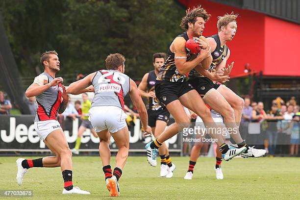 Ty Vickery of the Tigers marks the ball next to Jack Riewoldt against Tayte Pears and Cale Hooker of the Bombers during an AFL Practice Match between...