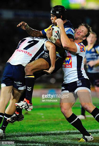 Ty Williams of the Cowboys is lifted by the Bronco defence of David Stagg and Joel Moon during the round 19 NRL match between the North Queensland...