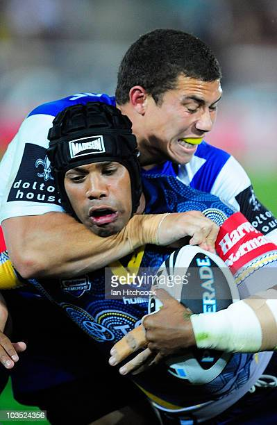 Ty Williams of the Cowboys is tackled by Daniel Rauicava of the Bulldogs XXXX during the round 24 NRL match between the North Queensland Cowboys and...