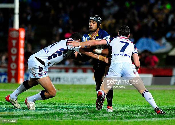 Ty Williams of the Cowboys is tackled by Willie Mason and Mitchell Pearce of the Roosters during the round 21 NRL match between the North Queensland...