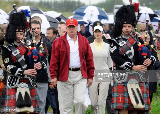 US tycoon Donald Trump is escorted by Scottish pipers as he officially opens his new multimillion pound Trump International Golf Links course in...