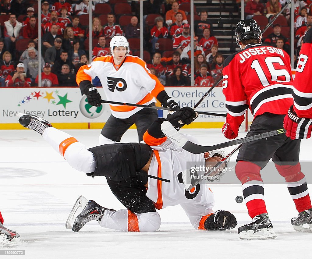 Tye Mcginn #15 of the Philadelphia Flyers is checked to the ice by Jacob Josefson #16 of the New Jersey Devils during the third period of an NHL hockey game at Prudential Center on November 2, 2013 in Newark, New Jersey.