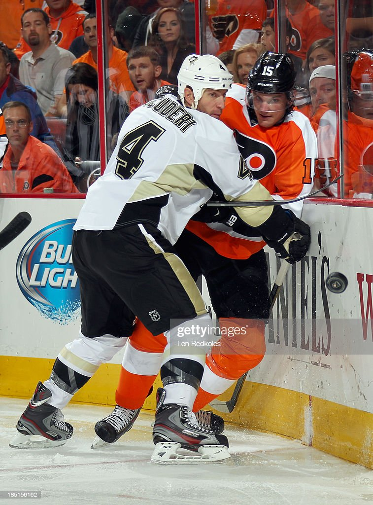 Tye McGinn #15 of the Philadelphia Flyers is pinned to the boards behind the net by Rob Scuderi #4 of the Pittsburgh Penguins on October 17, 2013 at the Wells Fargo Center in Philadelphia, Pennsylvania. The Penguins went on to defeat the Flyers 4-1.
