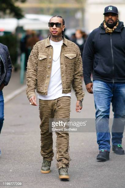 Tyga wears a khaki jacket, a white t-shirt, a chain necklace, sunglasses, outside Y Project, during Paris Fashion Week - Menswear F/W 2020-2021 : Day...