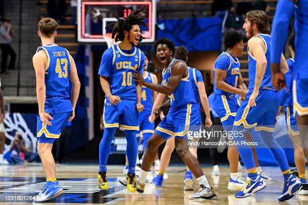 Tyger Campbell and David Singleton of the UCLA Bruins celebrate a victory over the Michigan State Spartans in the First Four round of the 2021 NCAA...