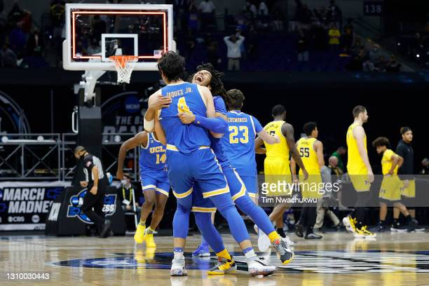Tyger Campbell of the UCLA Bruins celebrates with Jaime Jaquez Jr. #4 after defeating the Michigan Wolverines 51-49 in the Elite Eight round game of...