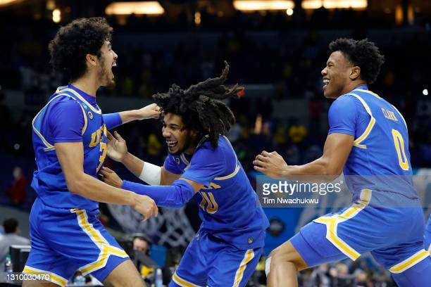 Tyger Campbell of the UCLA Bruins celebrates with Johnny Juzang and Jaylen Clark after defeating the Michigan Wolverines 51-49 in the Elite Eight...