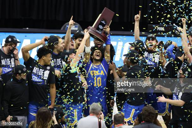 Tyger Campbell of the UCLA Bruins celebrates with the East Regional Champion trophy after defeating the Michigan Wolverines 51-49 in the Elite Eight...