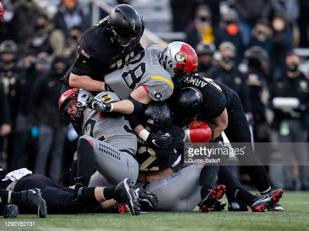 Tyhier Tyler of the Army Black Knights is tackled during the second quarter of a game against the Air Force Falcons at Michie Stadium on December 19,...