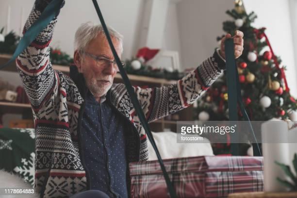 ateando un arco en un regalo de navidad - decoración objeto fotografías e imágenes de stock