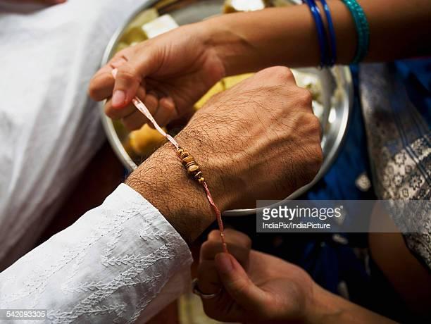 tying a rakhi on a wrist - raksha bandhan stock photos and pictures