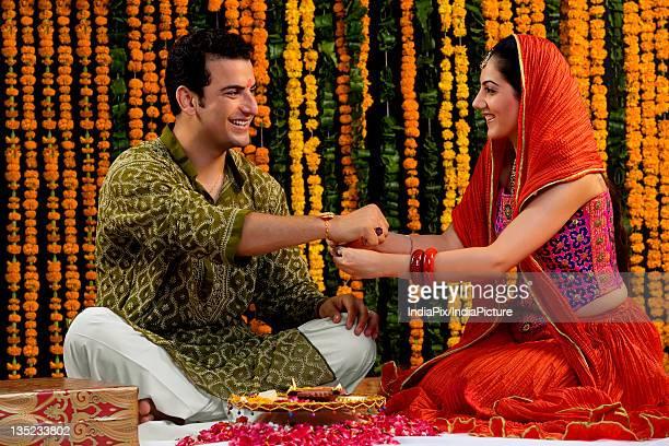 tying a rakhi - raksha bandhan stock photos and pictures