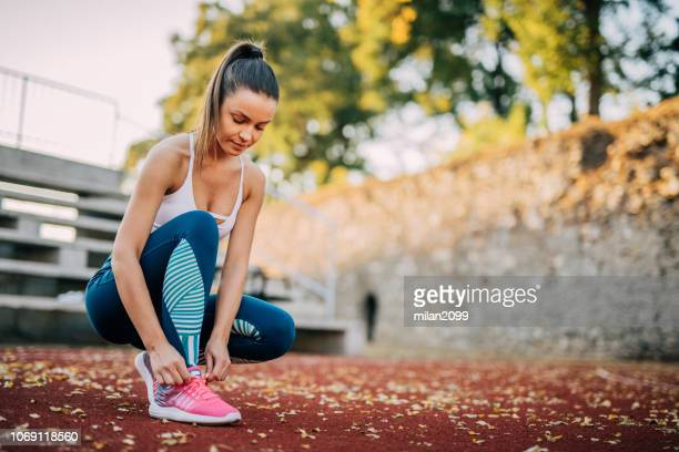 tying a shoelace - shoelace stock pictures, royalty-free photos & images