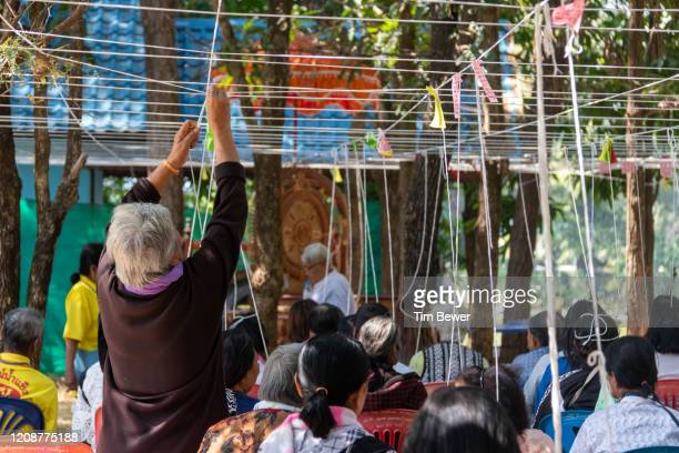 tying sacred threads during buddhist ceremony. - tim bewer fotografías e imágenes de stock
