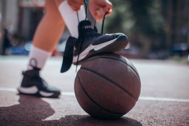 tying shoelace before game - basketball sneakers close up stock pictures, royalty-free photos & images