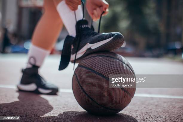 tying shoelace before game - basketball shoe stock photos and pictures