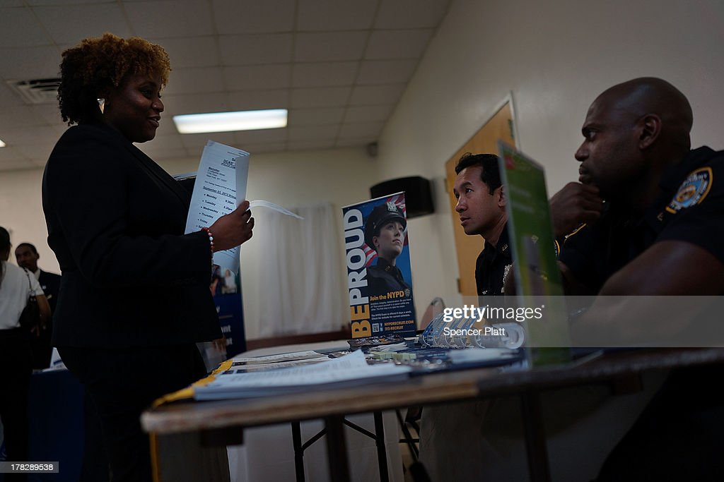 Tyira Singleton speaks with recruiters from the New York Police Department (NYPD) at the 'Beyond the Dream' job fair at the Brown Memorial Baptist Church in Clinton Hill, Brooklyn on August 28, 2013 in New York City. A new report by the Fiscal Policy Institute on New York's economy calls the last 10 years a 'lost decade' for typical workers. The report by the nonpartisan think tank found that median wages dropped almost 7 percent for men and about 1 percent for women.