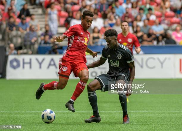 Tyler Adams of New York Red Bulls and Alphonso Davies of Vancouver Whitecaps compete for the ball at BC Place on August 18 2018 in Vancouver Canada