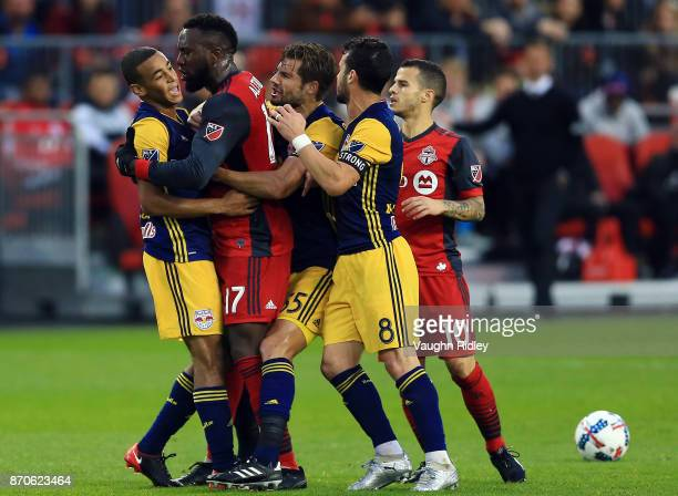 Tyler Adams of New York Red Bulls is held back by Jozy Altidore of Toronto FC during the first half of the MLS Eastern Conference Semifinal Leg 2...