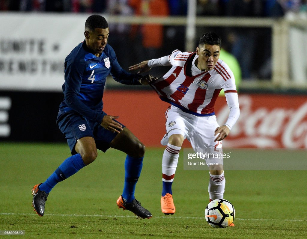 Tyler Adams #4 of United States grabs Miguel Almiron #23 of Paraguay as they battle for the ball during their game at WakeMed Soccer Park on March 27, 2018 in Cary, North Carolina.