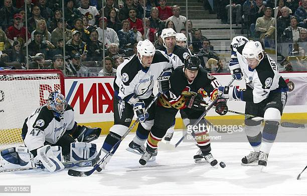 Tyler Arnason of the Ottawa Senators tries to move around the defense of goaltender John Grahame Cory Sarich and Evgeny Artyukhin of the Tampa Bay...