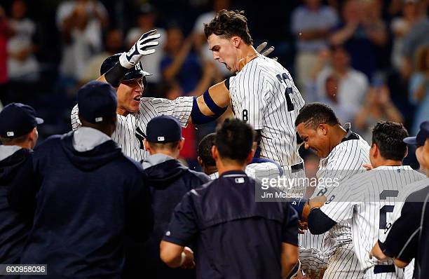 Tyler Austin of the New York Yankees celebrates his ninth inning game winning home run against the Tampa Bay Rays with his teammates at Yankee...