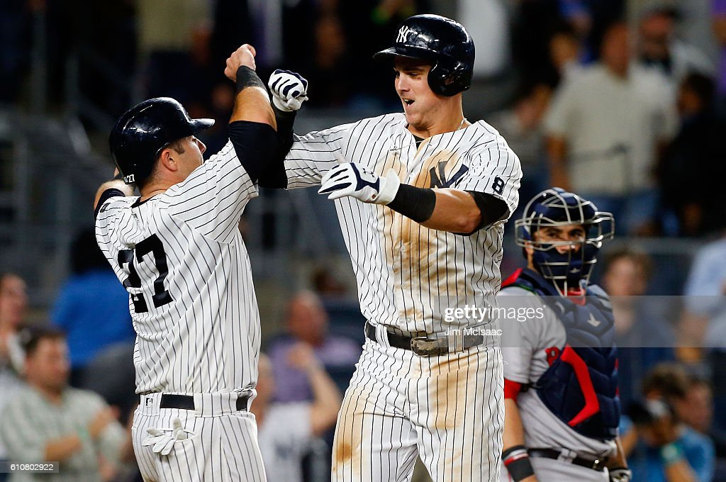 Tyler Austin #26 of the New York Yankees celebrates his seventh inning two-run home run with teammate Austin Romine #27 as Sandy Leon #3 of the Boston Red Sox looks on at Yankee Stadium on September 27, 2016 in the Bronx borough of New York City.