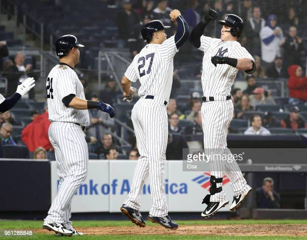 Tyler Austin of the New York Yankees celebrates his three run home run with teammates Giancarlo Stanton#27 and Gary Sanchez after Austin drove them...