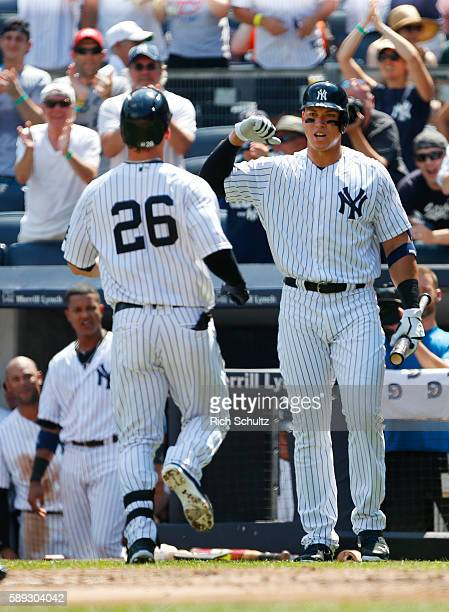 Tyler Austin of the New York Yankees is congratulated by Aaron Judge after Austin hit a home run in his first MLB at bat during the second inning of...