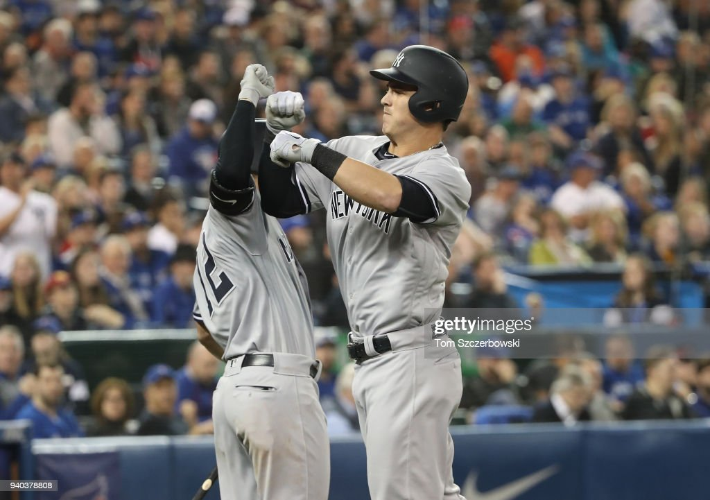 Tyler Austin #26 of the New York Yankees is congratulated by Tyler Wade #12 after hitting a two-run home run in the fifth inning during MLB game action against the Toronto Blue Jays at Rogers Centre on March 31, 2018 in Toronto, Canada.