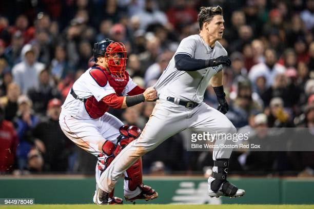 Tyler Austin of the New York Yankees is held back by Christian Vazquez as he charges the mound after being hit by a pitch by Joe Kelly of the Boston...