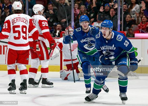 Tyler Bertuzzi and Niklas Kronwall of the Detroit Red Wings look on dejected as Bo Horvat of the Vancouver Canucks is congratulated by teammate Elias...