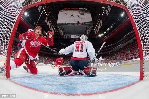 Tyler Bertuzzi of the Detroit Red Wings battles in front of the net next to goaltender Philipp Grubauer of the Washington Capitals during an NHL game...