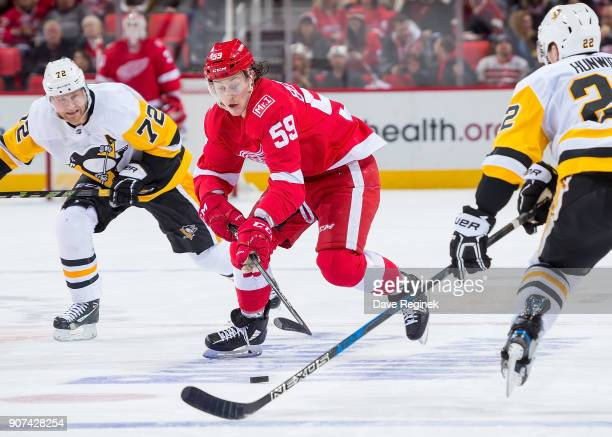 Tyler Bertuzzi of the Detroit Red Wings skates up ice with the puck in front of Patric Hornqvist of the Pittsburgh Penguins during an NHL game at...
