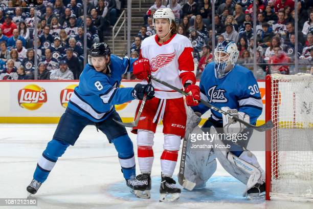 Tyler Bertuzzi of the Detroit Red Wings stands between Jacob Trouba and goaltender Laurent Brossoit of the Winnipeg Jets as they keep an eye on the...