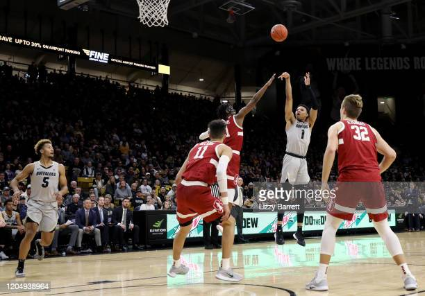 Tyler Bey of the Colorado Buffaloes shoots over the defense of Daejon Davis of the Stanford Cardinal during the second half in a game between the...