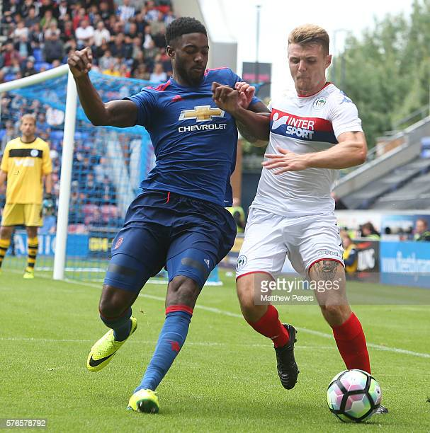 Tyler Blackett of Manchester United in action with David Perkins of Wigan Athletic during the pre-season friendly match between Wigan Athletic and...