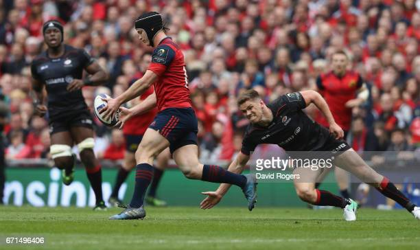 Tyler Bleyendaal of Munster is tackled by Owen Farrell during the European Rugby Champions Cup semi final match between Munster and Saracens at the...