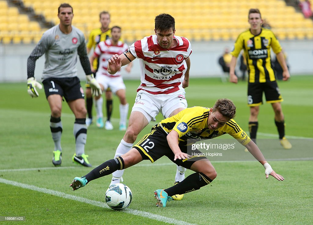 Tyler Boyd of the Phoenix attempts to keep the ball in play while Michael Beauchamp of the Wanderers looks on during the round 16 A-League match between the Wellington Phoenix and the Western Sydney Wanderers at Westpac Stadium on January 13, 2013 in Wellington, New Zealand.