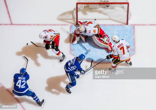 Tyler Bozak and James van Riemsdyk go to the net against Mike Smith TJ Brodie and Travis Hamonic of the Calgary Flames during the first period at the...