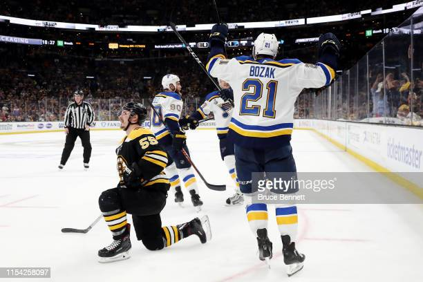 Tyler Bozak of the St. Louis Blues celebrates a goal by teammate David Perron after tripping up Noel Acciari of the Boston Bruins during the third...